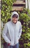 Ευτυχής νεαρός άνδρας που φορά ένα hoodie και ένα καπέλο του μπέιζμπολ Στοκ φωτογραφίες με δικαίωμα ελεύθερης χρήσης