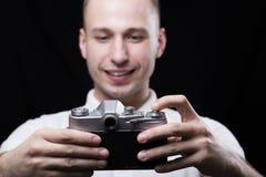 Ευτυχής νεαρός άνδρας που φωτογραφίζεται στην παλαιά κάμερα Στοκ φωτογραφία με δικαίωμα ελεύθερης χρήσης
