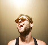 Ευτυχής νεαρός άνδρας που χαμογελά με τα γυαλιά ηλίου Στοκ Φωτογραφία