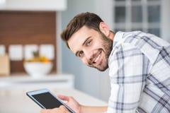 Ευτυχής νεαρός άνδρας που χρησιμοποιεί την ψηφιακή ταμπλέτα Στοκ Εικόνες