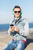 Ευτυχής νεαρός άνδρας στα ακουστικά με το smartphone Στοκ Φωτογραφία