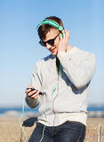 Ευτυχής νεαρός άνδρας στα ακουστικά με το smartphone Στοκ εικόνες με δικαίωμα ελεύθερης χρήσης