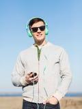 Ευτυχής νεαρός άνδρας στα ακουστικά με το smartphone Στοκ Εικόνες
