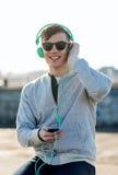 Ευτυχής νεαρός άνδρας στα ακουστικά με το smartphone Στοκ εικόνα με δικαίωμα ελεύθερης χρήσης