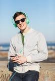 Ευτυχής νεαρός άνδρας στα ακουστικά με το smartphone Στοκ Φωτογραφίες