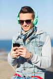 Ευτυχής νεαρός άνδρας στα ακουστικά με το smartphone Στοκ φωτογραφίες με δικαίωμα ελεύθερης χρήσης