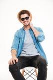 Ευτυχής νεαρός άνδρας στο καπέλο και γυαλιά ηλίου που κάθονται στην καρέκλα Στοκ εικόνες με δικαίωμα ελεύθερης χρήσης