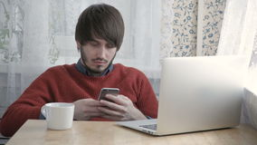 Ευτυχής νεαρός άνδρας Freelancer που εργάζεται με το σύγχρονα lap-top και το τηλέφωνο στον καφέ που παίρνει το φλιτζάνι του καφέ απόθεμα βίντεο
