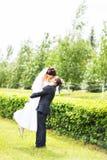 Ευτυχής νεόνυμφος που κρατά τη νέα όμορφη νύφη στα όπλα του Στοκ φωτογραφία με δικαίωμα ελεύθερης χρήσης