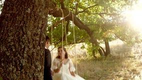 Ευτυχής νεόνυμφος που ταλαντεύεται στη νύφη ταλάντευσης στο όμορφο άσπρο φόρεμα στο θερινό πάρκο ταλάντευση στον κλάδο μιας βαλαν φιλμ μικρού μήκους