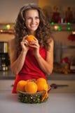 Ευτυχής νοικοκυρά με τα πορτοκάλια διακοσμημένη στη Χριστούγεννα κουζίνα Στοκ Εικόνες