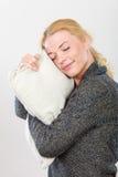 Ευτυχής νυσταλέα εκμετάλλευση γυναικών και αγκάλιασμα του μαξιλαριού Στοκ Εικόνες
