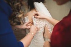 Ευτυχής νύφη βοηθειών φιλαράκων που παίρνει έτοιμη για τη ημέρα γάμου της το πρωί Στοκ Εικόνες