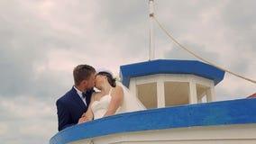 Ευτυχής νύφη με το νεόνυμφο που πλέει με το σκάφος Κάτω από το τιμόνι του νεαρού άνδρα απόθεμα βίντεο