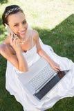 Ευτυχής νύφη με το lap-top που χρησιμοποιεί το κινητό τηλέφωνο στη χλόη στοκ φωτογραφία