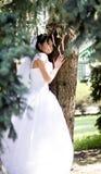 Ευτυχής νύφη που χαμογελά κοντά στο θερινό δέντρο υπαίθρια Στοκ Φωτογραφία