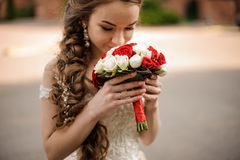 Ευτυχής νύφη σε ένα γαμήλιο φόρεμα με μια πλεξούδα hairstyle που ρουθουνίζει μια ανθοδέσμη των τριαντάφυλλων στοκ φωτογραφίες