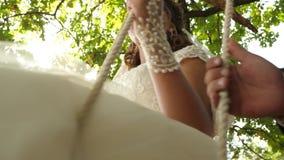 Ευτυχής νύφη στο άσπρο φόρεμα που ταλαντεύεται στην ταλάντευση στο πάρκο σε έναν κλάδο μιας βαλανιδιάς Κινηματογράφηση σε πρώτο π απόθεμα βίντεο