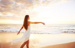 Ευτυχής ξένοιαστη γυναίκα στην παραλία στο ηλιοβασίλεμα Στοκ Φωτογραφία