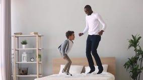 Ευτυχής ξένοιαστος αφρικανικός γιος πατέρων και παιδιών που πηδά στο κρεβάτι απόθεμα βίντεο
