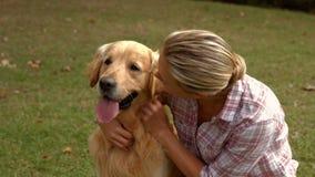 Ευτυχής ξανθή γυναίκα με το σκυλί της στο πάρκο απόθεμα βίντεο