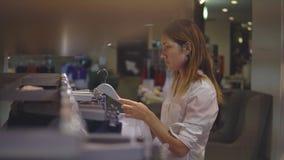 Ευτυχής ξανθή γυναίκα που επιλέγει τον ιματισμό στο κατάστημα απόθεμα βίντεο