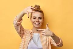 Ευτυχής ξανθή γυναίκα που καθιστά το πλαίσιο με τα δάχτυλα απομονωμένο στο κίτρινο υπόβαθρο στοκ φωτογραφία