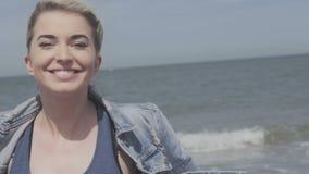 Ευτυχής ξανθή γυναίκα στο σακάκι τζιν που στέλνει ένα φιλί στη μόνη παραλία απόθεμα βίντεο