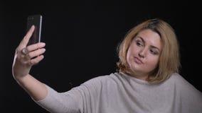 Ευτυχής ξανθή με κοντά μαλλιά υπέρβαρη επιχειρηματίας που κάνει τις selfie-φωτογραφίες φλερτ που χρησιμοποιούν το smartphone στο  απόθεμα βίντεο