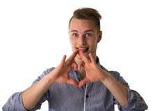 Ευτυχής ξανθός νεαρός άνδρας που κάνει την καρδιά ή το πνεύμα σημαδιών αγάπης Στοκ Εικόνα