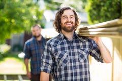 Ευτυχής ξυλουργός με τις φέρνοντας σανίδες συναδέλφων στοκ φωτογραφία