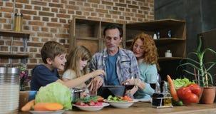 Ευτυχής οθόνη αφής ταμπλετών οικογενειακής χρήσης ψηφιακή στην κουζίνα μαγειρεύοντας τους γονείς γευμάτων με δύο παιδιά που μιλού απόθεμα βίντεο