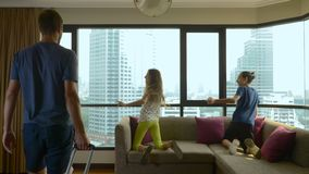 Ευτυχής οικογένεια, γυναίκα, άνδρας και δύο παιδιά με μια βαλίτσα στο υπόβαθρο των ουρανοξυστών σε ένα πανοραμικό παράθυρο φιλμ μικρού μήκους