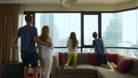 Ευτυχής οικογένεια, γυναίκα, άνδρας και δύο παιδιά με μια βαλίτσα στο υπόβαθρο των ουρανοξυστών σε ένα πανοραμικό παράθυρο στοκ φωτογραφία με δικαίωμα ελεύθερης χρήσης