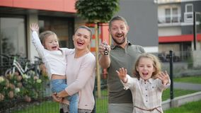 Ευτυχής οικογένεια κοντά στο καινούργιο σπίτι τους κτήμα έννοιας πραγματικό Έχουν πολλή διασκέδαση από κοινού απόθεμα βίντεο