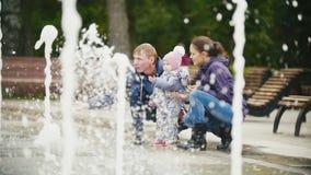 Ευτυχής οικογένεια - κόρη μητέρων, πατέρων και μωρών κοντά στις πηγές στο πάρκο πόλεων, σε αργή κίνηση φιλμ μικρού μήκους