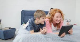 Ευτυχής οικογένεια μαζί στη μητέρα και το γιο κρεβατοκάμαρων που χρησιμοποιούν τον υπολογιστή ταμπλετών πέρα από το αγκάλιασμα το απόθεμα βίντεο