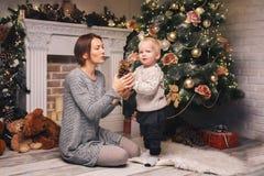 Ευτυχής οικογένεια μεταξύ των διακοσμήσεων Χριστουγέννων στο σπίτι Στοκ Εικόνα