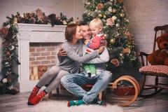 Ευτυχής οικογένεια μεταξύ των διακοσμήσεων Χριστουγέννων στο σπίτι Στοκ εικόνα με δικαίωμα ελεύθερης χρήσης