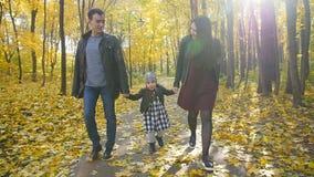Ευτυχής οικογένεια με έναν μικρό περίπατο κορών στο πάρκο φθινοπώρου απόθεμα βίντεο