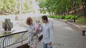 Ευτυχής οικογένεια με ένα μικρό παιδί που περπατά στο πάρκο απόθεμα βίντεο