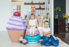 Ευτυχής οικογένεια με δύο παιδιά και το μεγάλο παγωτό 3 οικογενειακά κορίτσια καναπέδων φωτογραφικών μηχανών που φαίνονται πορτοκ Στοκ Εικόνα