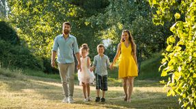 Ευτυχής οικογένεια με δύο παιδιά που κρατούν τα χέρια κατά τη διάρκεια του ψυχαγωγικού περιπάτου στοκ φωτογραφίες με δικαίωμα ελεύθερης χρήσης