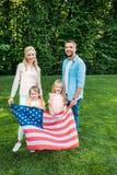 ευτυχής οικογένεια με δύο παιδιά που κρατούν τη αμερικανική σημαία και που χαμογελούν στη κάμερα στο πάρκο στοκ φωτογραφίες