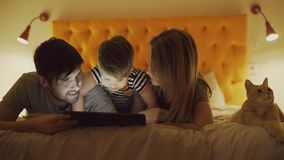Ευτυχής οικογένεια με λίγο γιο και την αστεία γάτα που βρίσκονται στο κρεβάτι στο σπίτι και που χρησιμοποιούν τον υπολογιστή ταμπ στοκ φωτογραφία