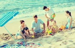 Ευτυχής οικογένεια με τέσσερα παιδιά που παίζουν στην παραλία Στοκ Φωτογραφίες