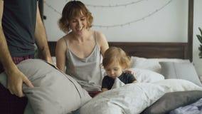 Ευτυχής οικογένεια με τα νέα χαριτωμένα μαξιλάρια παιχνιδιού και πάλης κορών στο κρεβάτι στο σπίτι απόθεμα βίντεο