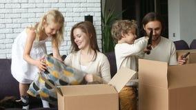 Ευτυχής οικογένεια με τα παιδιά που ανοίγουν τα κιβώτια που κινούνται στο νέο σπίτι απόθεμα βίντεο