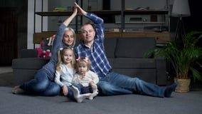 Ευτυχής οικογένεια με τα παιδιά που παρουσιάζουν στέγη του σπιτιού απόθεμα βίντεο