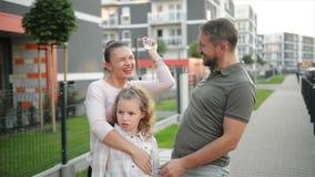 Ευτυχής οικογένεια με τα παιδιά που στέκονται τα υπαίθρια κλειδιά εκμετάλλευσης του μεγάλου εξοχικού σπιτιού Χαμογελώντας ζεύγος  απόθεμα βίντεο